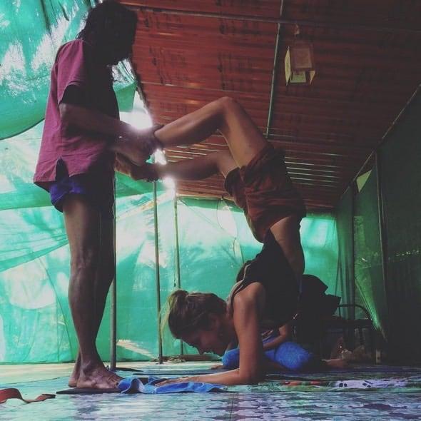 Min yogalärare Krishna hjälper mig in i en yogaposition