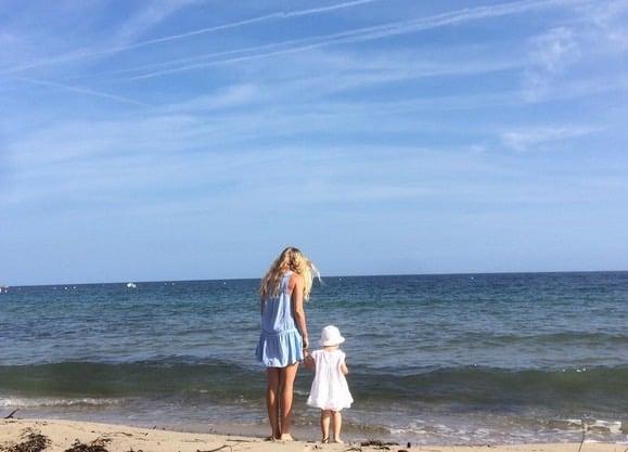 Yogaläraren Johanna Andersson på stranden med sin dotter.