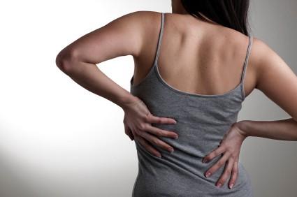 Kvinna som har ont i ryggen